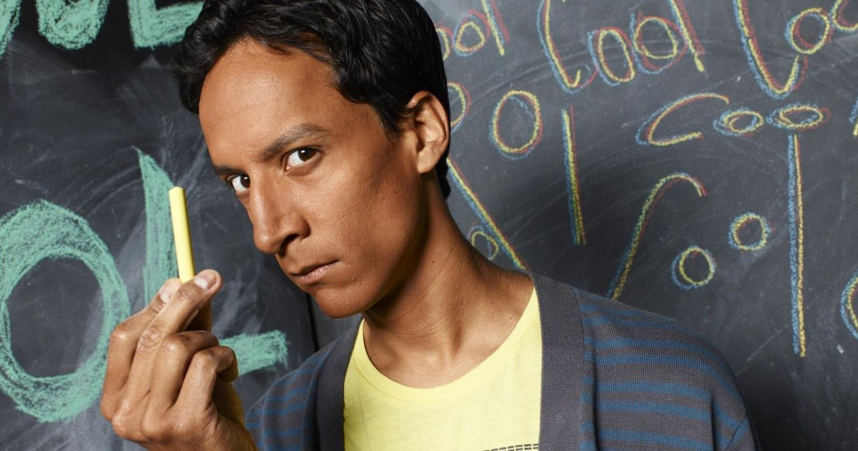 Photo of Danny Pudi as Abed from Community, holding up a piece of chalk and standing in front of a chalkboard.