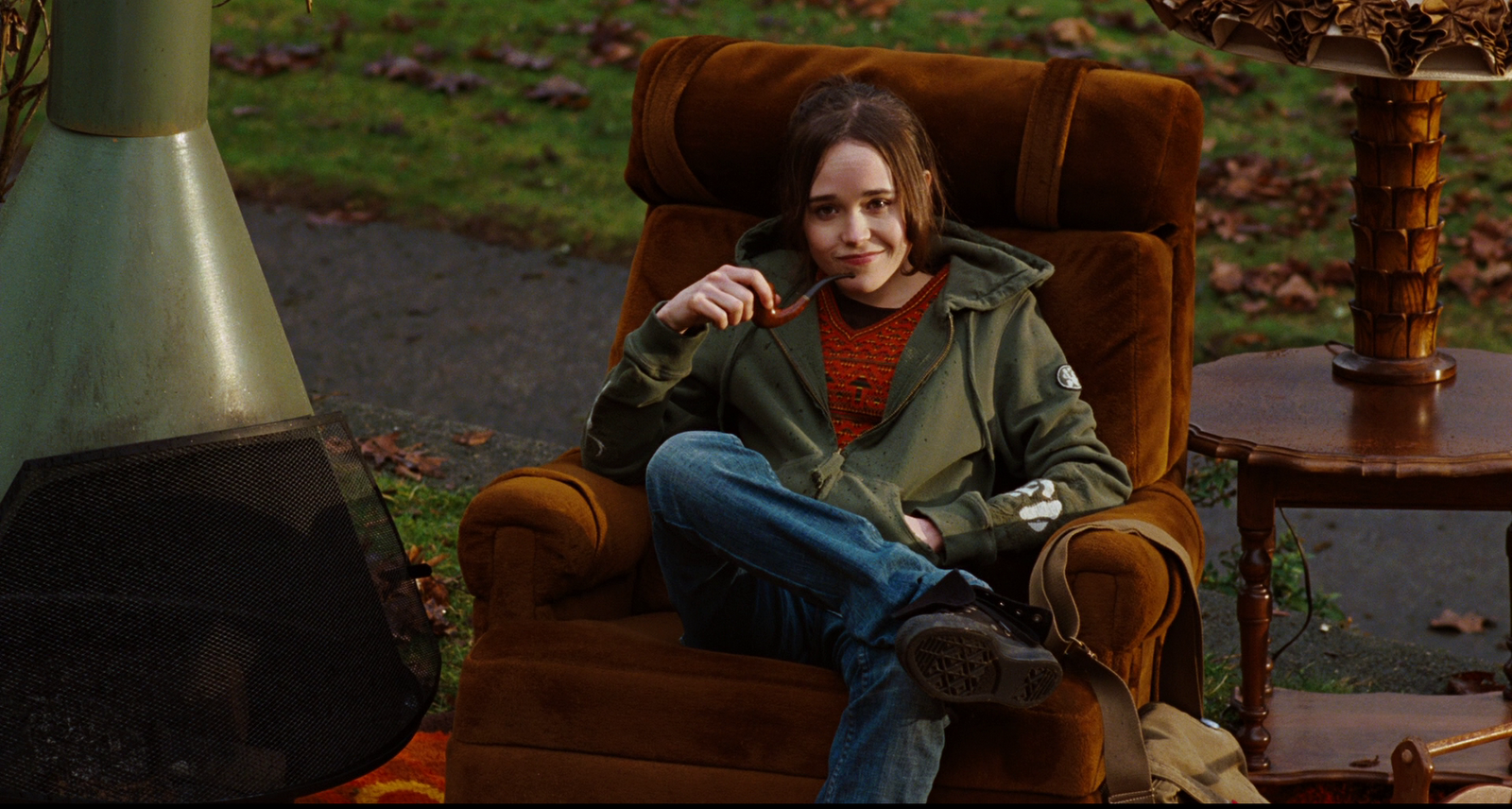 Photo of Elliott Page as Juno, sitting on a chair with a pipe in her hand.